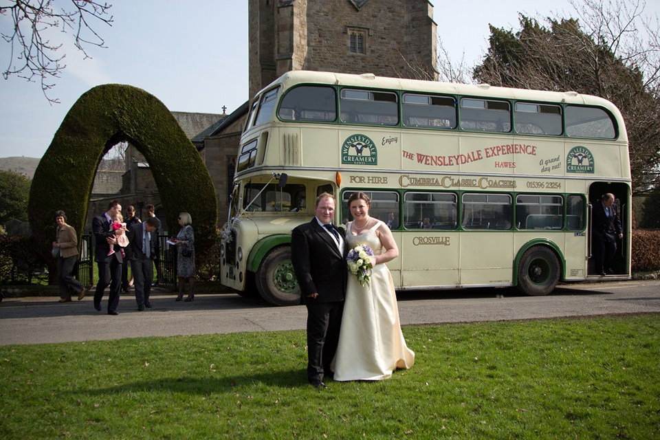 Bride & Groom Standing in front of bus outside church