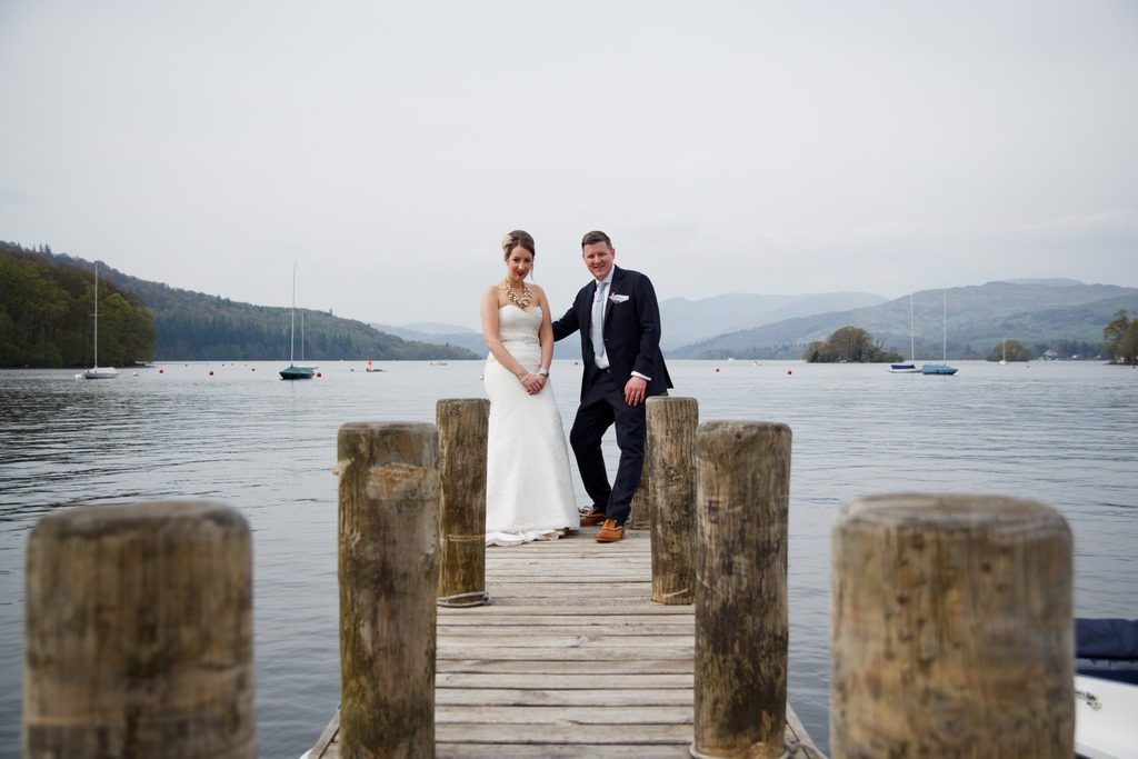 bride rebecca and groom brendan stand on jetty over windermere