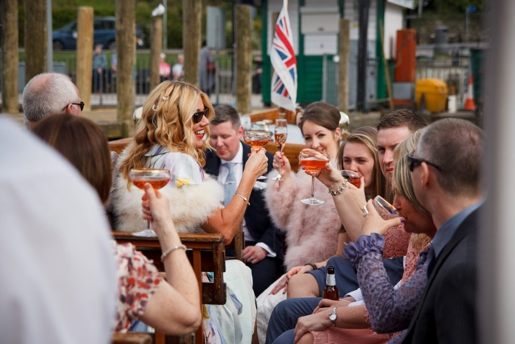 wedding guests raising a glass of champagne on the boat