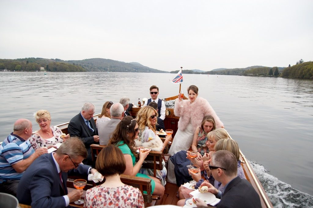 bride rebecca stood at the front of boat raising a glass of champagne